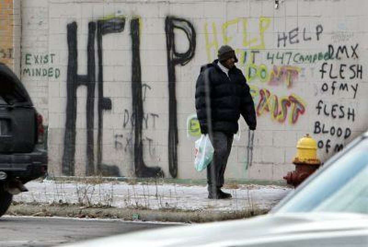 A pedestrian walks by graffiti in downtown Detroit. Michigan Gov. Rick Snyder appointed an emergency manager for the city and approved its bankruptcy filing.