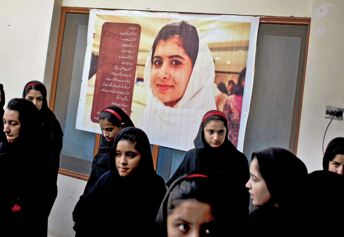In this Thursday, Nov. 15, 2012 photo, Pakistani girls gather under a poster of Malala Yousufzai in her old school in Mingora, Swat Valley, Pakistan. The giant poster of her that once emblazoned the wall of the assembly hall has been removed. The school made no plans to recognize the anniversary of Malala's shooting by Taliban, teachers and students are afraid. (AP Photo/Anja Niedringhaus)