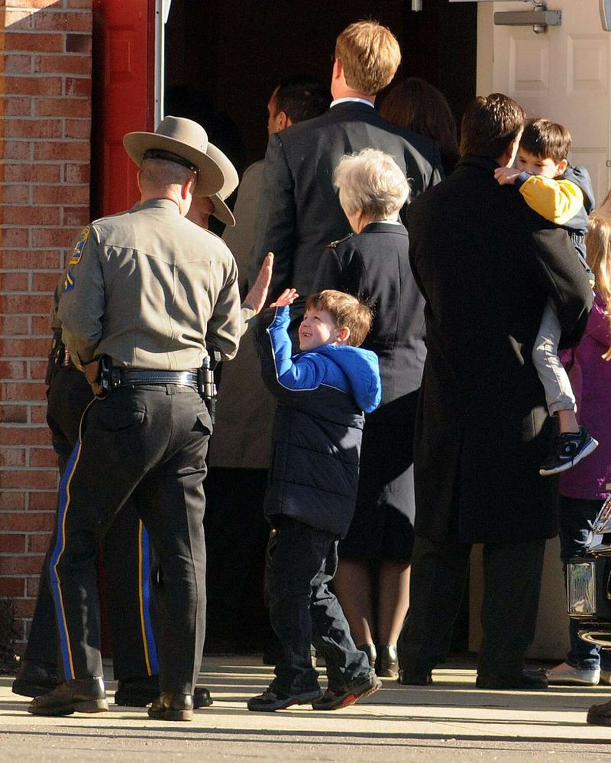 A little boy gets a high-five greeting from a State Trooper before Charlotte Bacon's funeral at Christ the King Lutheran Church, Newtown. Mara Lavitt/New Haven Register12/19/12