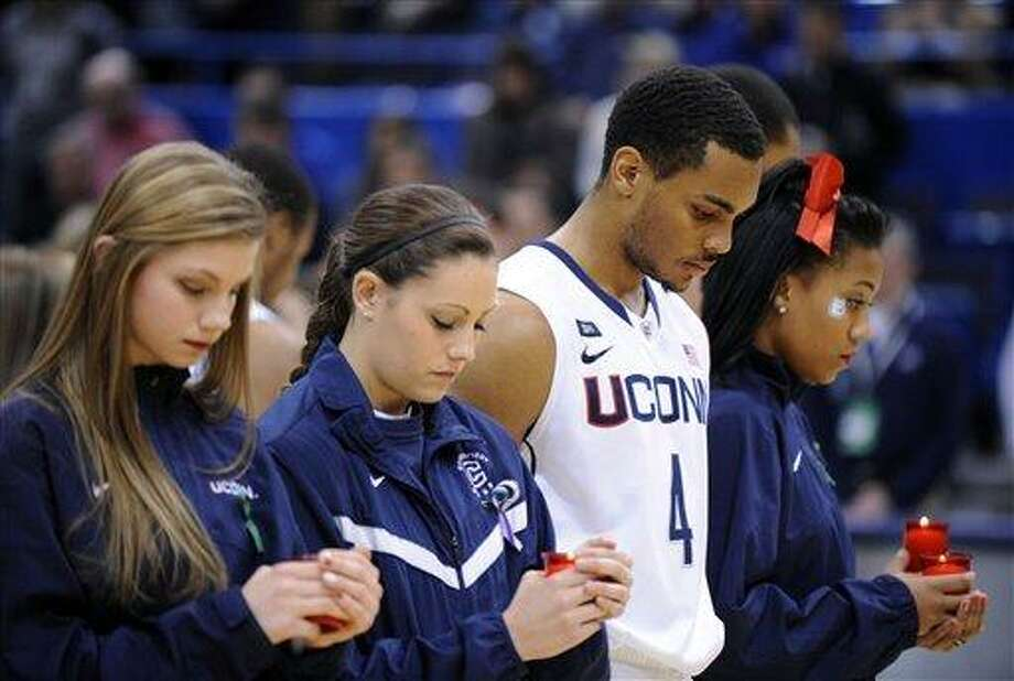 Members of the Connecticut's cheer, dance and basketball teams participate in a service honoring those killed in a school shooting in Newtown, Conn., last Friday. The service was held before an NCAA college basketball game between Connecticut and Maryland Eastern Shore in Hartford, Conn., Monday, Dec. 17, 2012. (AP Photo/Fred Beckham) Photo: ASSOCIATED PRESS / AP2012