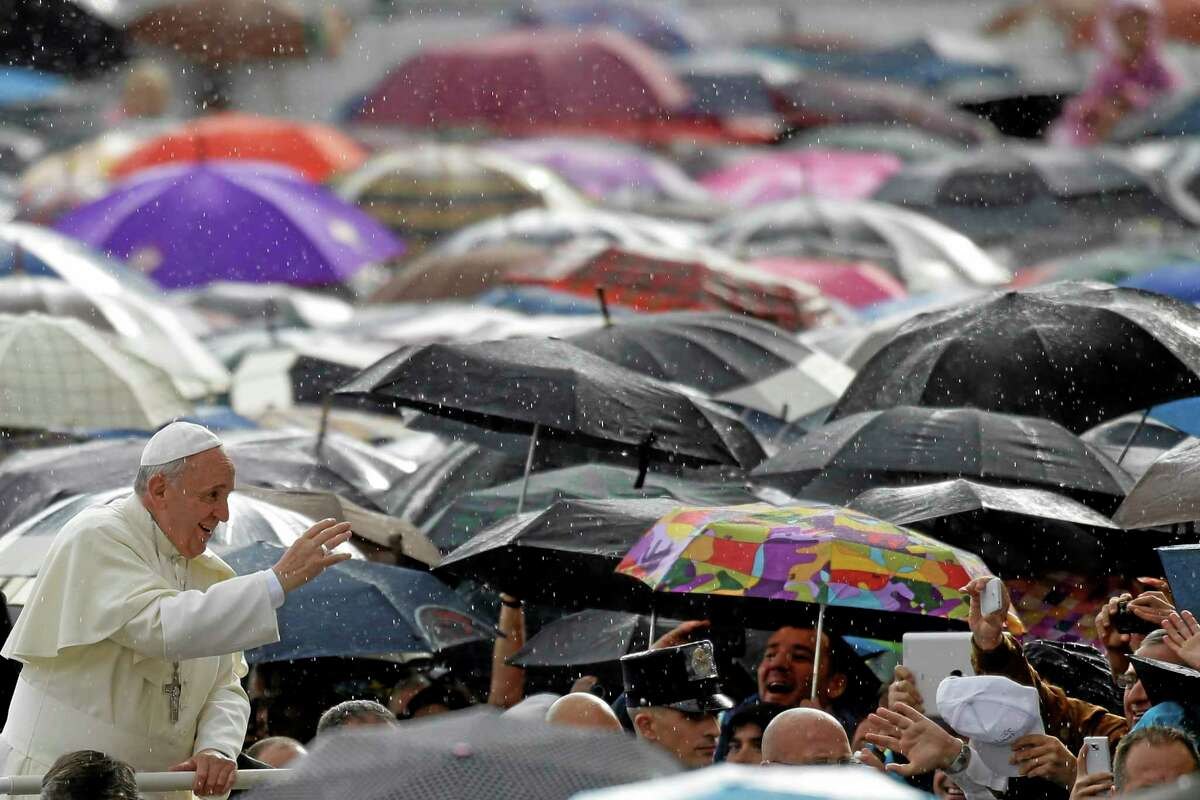 Under a light rain Pope Francis blesses the faithful in St. Peter's Square during the weekly general audience at the Vatican, Wednesday, Oct. 9, 2013. (AP Photo/Gregorio Borgia)