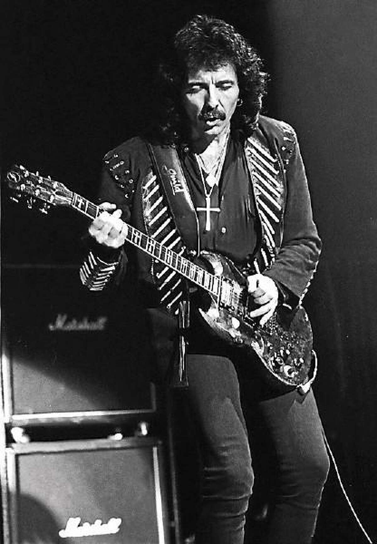 """Black Sabbath guitarist Tony Iommi is shown performing during a """"live"""" concert appearance."""