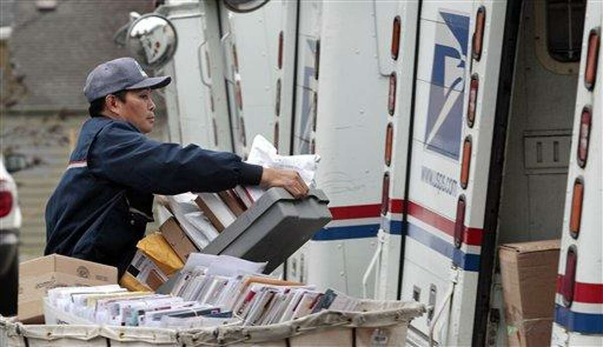 This Dec. 5, 2011 file photo shows letter carrier Diosdado Gabnat moving boxes of mail into his truck to begin delivery at a post office in Seattle. Americans for generations have come to depend on door-to-door mail delivery. It?s about as American as apple pie. But with the Postal Service facing billions of dollars in annual losses, the long-cherished delivery service could be virtually phased-out by 2022 under a proposal a House panel was considering Wednesday. Curbside delivery, which includes deliveries to mailboxes at the end of driveways, and cluster box delivery would replace letter carriers slipping mail into front-door boxes. (AP Photo/Elaine Thompson, File)