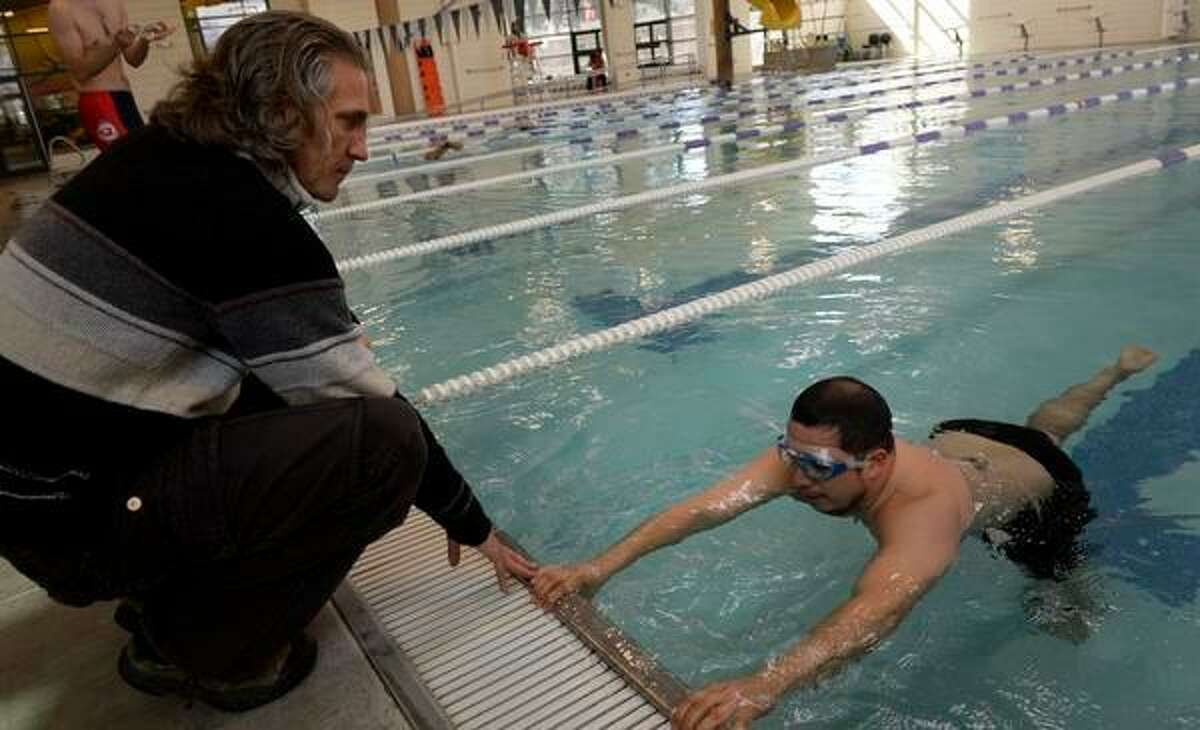 DENVER, CO- MARCH 6: Aspiring triathlete John Sanchez, right, gets some stroke advice from swim coach David Saintsing, left, during his swimming workout at the North Boulder Recreation Center in Boulder, CO on March 7th, 2013. Sanchez is an aspiring new triathlete. He has two coaches that help him with his swimming when he get the opportunity to get to the pool. Sanchez hopes to do his first triathlon sometime this summer(Photo By Helen H. Richardson/ The Denver Post)