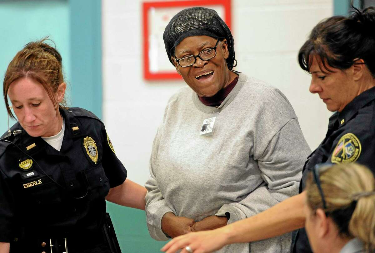 Bonnie Jean Foreshaw, center, smiles as she is led in for a clemency hearing at the J.B. Gates Correctional Institution, Wednesday, Oct. 9, 2013, in East Lyme, Conn. The 66-year-old Foreshaw is serving a 45-year prison sentence for premeditated murder for the killing of a pregnant woman, Joyce Amos, in 1986. (AP Photo/Jessica Hill)