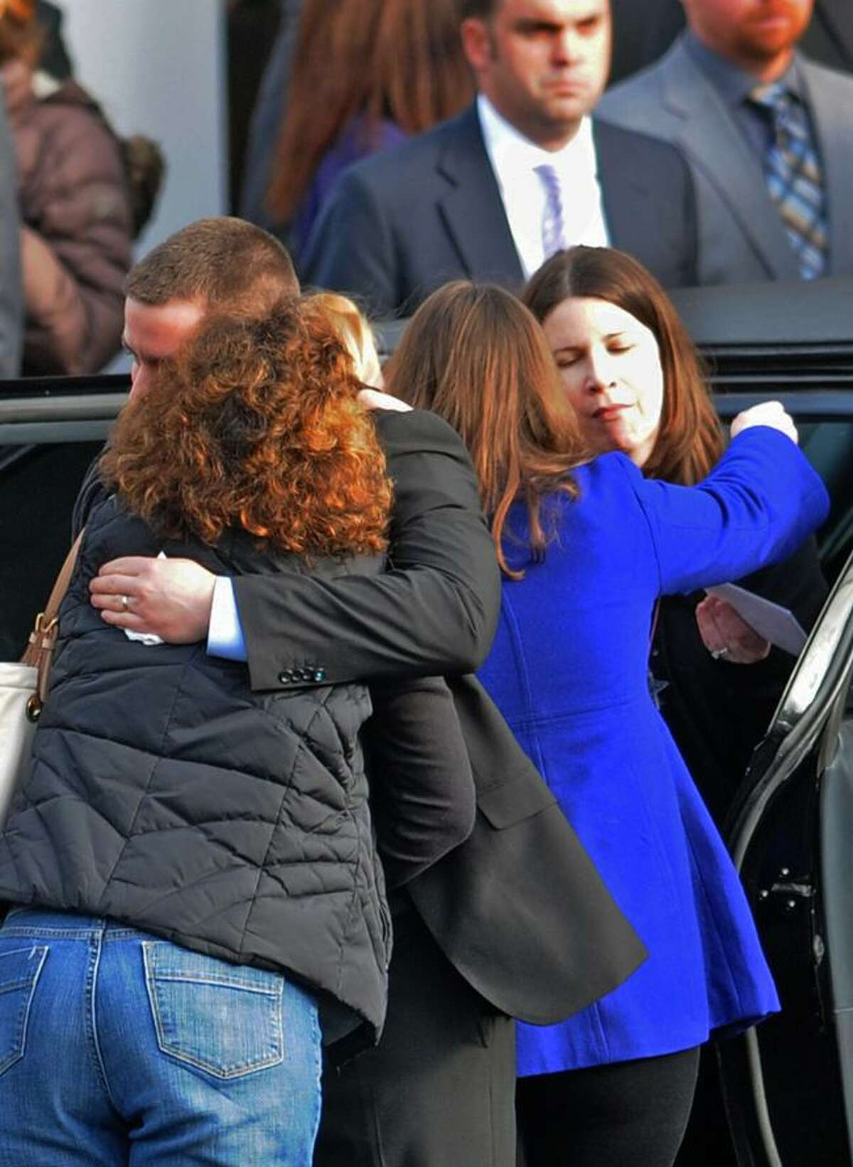 Rich Rekos, left, and his wife Krista Rekos, far right, hug mourners after the funeral of their daughter Jessica Rekos, 6, of Newtown at the St. Rose of Lima Roman Catholic church Tuesday morning December 18, 2012. Rekos was killed by a gunman who also claimed the lives of 6 adults and 19 other children at the Sandy Hooky Elementary School shooting Friday, December 15, 2012. Photo by Peter Hvizdak / New Haven Register
