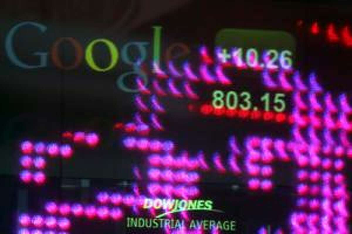 The Google logo and numbers are displayed on a ticker behind Time Square lights reflected on NASDAQ headquarters windows, Tuesday, Feb. 19, 2013 in New York. Google's stock price topped $800 for the first time Tuesday, Feb. 19, 2013, amid renewed confidence in the company's ability to reap steadily higher profits from its dominance of Internet search and prominence in the increasingly important mobile device market. (AP Photo/Mary Altaffer)