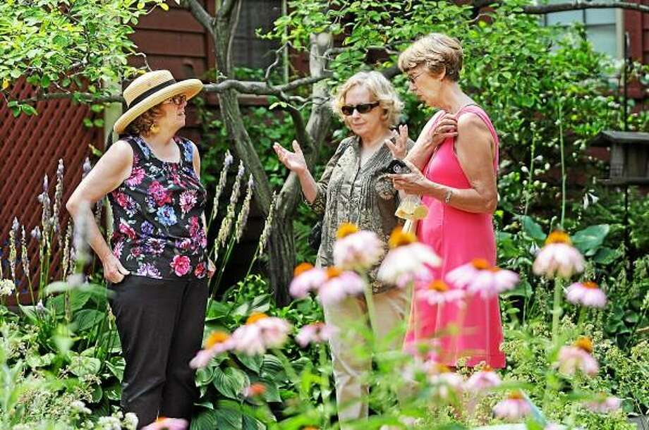 """Deborah Shapiro, Executive Director at the Middlesex County Historical Society in Middletown, at left chats with Higganum Martha McLaud Tonucci, at far right,  and Middletown resident Truda Steinnagel in the Mansfield House Gardens Wednesday afternoon following the """"Beautiful Brimming Blossoms At Our House"""" luncheon at the General Mansfield House, home to the Middlesex Historical Society on Main Street in Middletown. McLaud Tonucci Past is President of the CT Botanical Society and Steinnagel currently serves on the Board of Directors.  Catherine Avalone - The Middletown Press / TheMiddletownPress"""