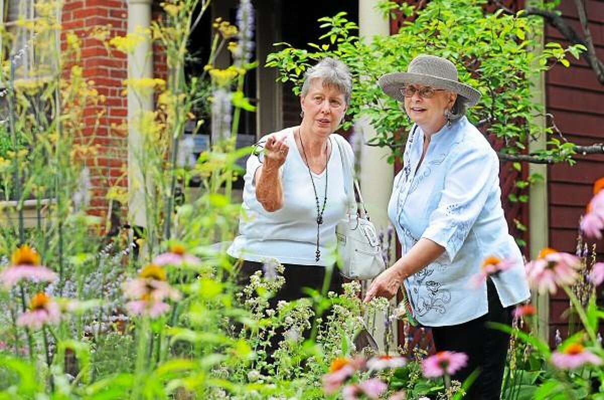 """Catherine Avalone - The Middletown Press Kathie Green, of Middlefield and Middletown resident Jane Harris walk through the Mansfield House Gardens Wednesday afternoon following the """"Beautiful Brimming Blossoms At Our House"""" luncheon at the General Mansfield House, home to the Middlesex Historical Society on Main Street in Middletown."""