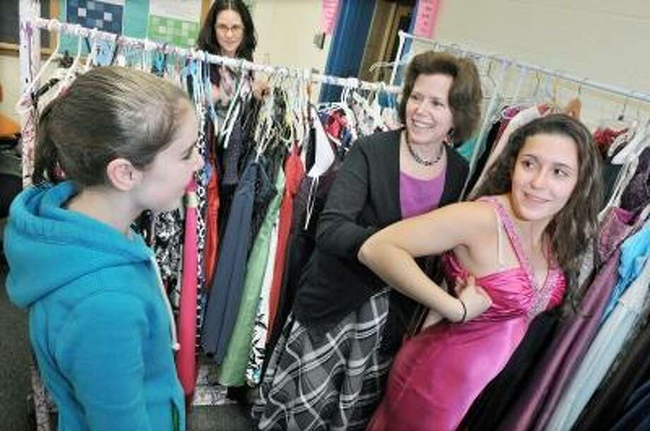 Catherine Avalone/The Middletown Press   Laura Roman, committee member of Haddam-Killingworth Project Graduation helps her 15-year-old daughter Danni Roman, a sophomore tries on prom dresses at the Project Graduation Gently Used Prom/Party Dress Sale. At left is Maddy Evans, 12, of Ivoryton who stopped in with her mom, Karen to try on dresses for her bat mitzvah. The sale includes dresses suitable for middle school through high school aged girls and is open to the public Saturday from 10 a.m. - 4 p.m. at the old H-K Middle School gym on Little City Road in Higganum. Dresses will not exceed $50 and all proceeds benefit Project Graduation. / TheMiddletownPress