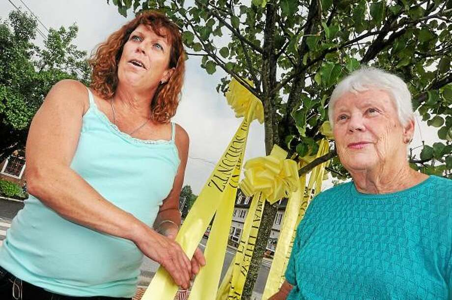 East Hampton resident Donna McLaughlin, at left holds the yellow ribbon for her son, Army Specialist Kurt Schluntz in the village center Tuesday evening. With her is her mother Ann McLaughlin, Schluntz's grandmother, the organizer of the Yellow Ribbon. / TheMiddletownPress