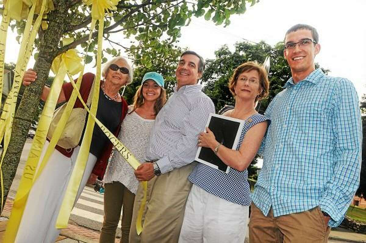 East Hampton residents Tom Rogers holds the yellow ribbon for his son, First Lt. Matthew Rogers in the United States Army with his wife, Lisa and their daughter Cathryn and son Brendan in the village center Tuesday afternoon. Also pictured is Matthew Rogers grandmother Carol, at left. Catherine Avalone - The Middletown Press