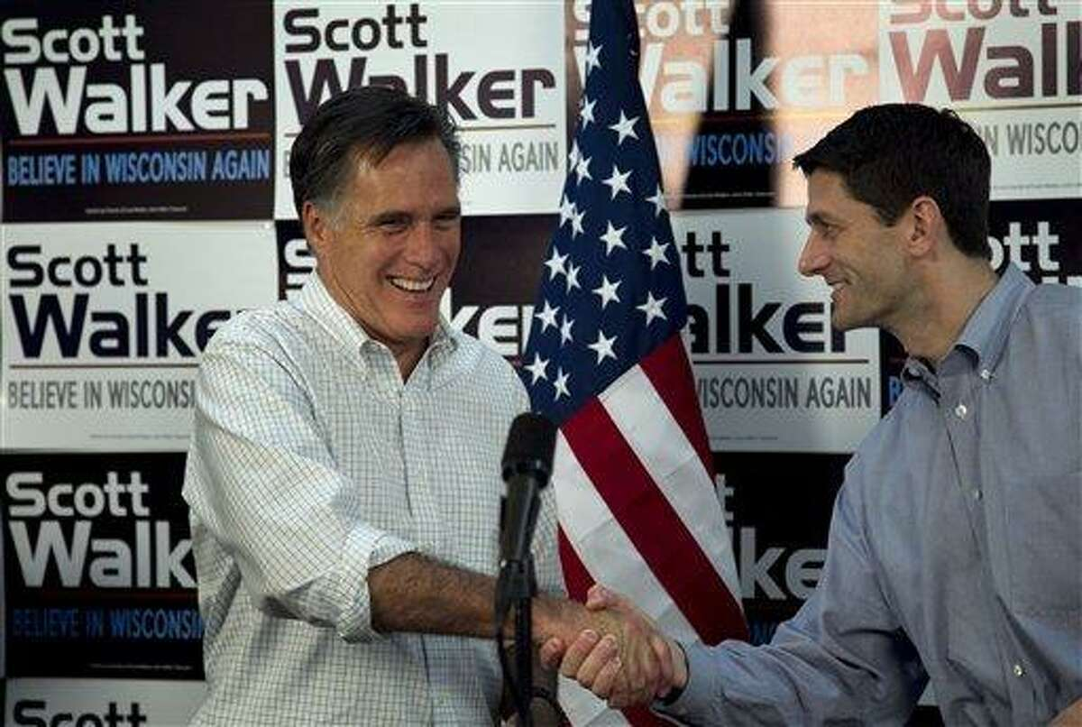 Republican presidential candidate, former Massachusetts Gov. Mitt Romney, left, shakes hands with U.S. Rep. Paul Ryan, R-Wis., Chairman of the House Budget Committee, right, before speaking with supporters of Wisconsin Republican Gov. Scott Walker at a phone bank during a campaign stop in Fitchburg, Wis., in this March file photo. Associated Press
