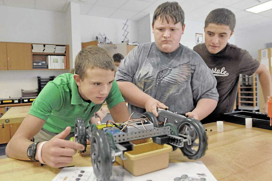 Middletown High School freshman Patrick Rious, 14, left, junior Chris Tucker, 16, center, and sophomore Ibrahim Elmali, 16, troubleshoot a problem with their robot's wheels Wednesday afternoon during class. The students are in Sam Faulkenberry's Robotics 1 class. Photo: Catherine Avalone — The Middletown Press  / TheMiddletownPress