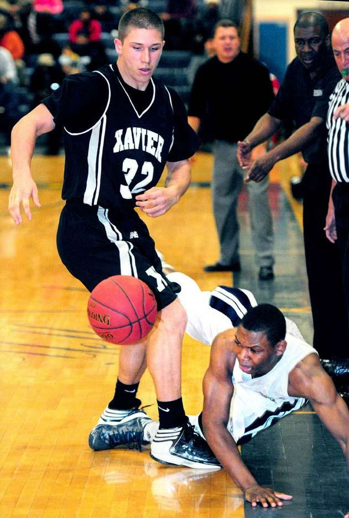 Joe Carbone (left) of Xavier guards Bobby Bynum (right) of HIllhouse as he goes out of bounds in the second half of the Class LL boys semifinal in East Haven on 3/12/2013. Photo by Arnold Gold/New Haven Register
