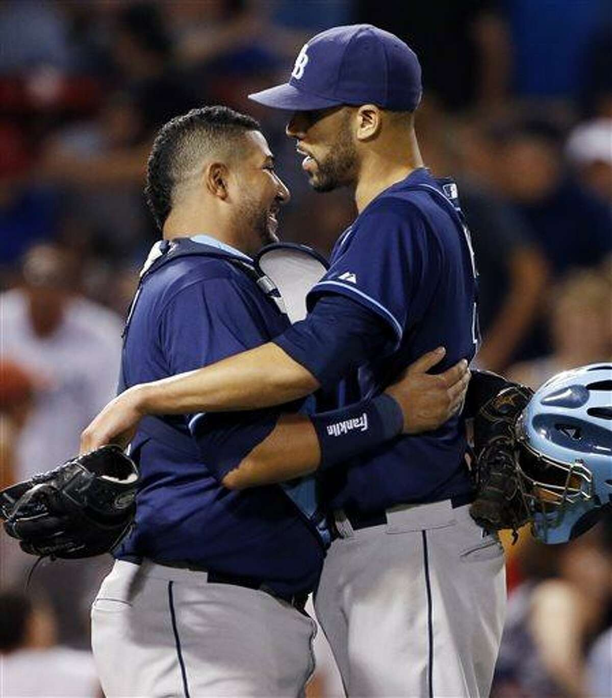 Tampa Bay Rays starting pitcher David Price, right, celebrates with catcher Jose Molina after throwing a five-hitter against the Boston Red Sox in a baseball game at Fenway Park in Boston Wednesday, July 24, 2013. The Rays won 5-1. (AP Photo/Elise Amendola)
