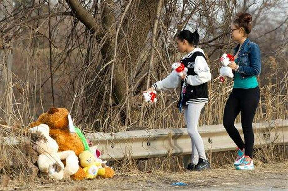 Dominique Ellison, left, and Rickie Bowling, of Warren, bring stuffed animals to a memorial in honor of their friends who died in a car crash on Park Ave. in Warren, Ohio on Sunday, March 10, 2013. (AP Photo/Scott R. Galvin) Photo: AP / FR170532 AP