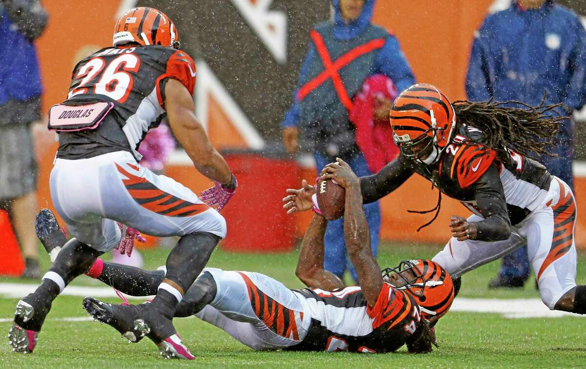 """Bengals cornerback Adam Jones, center, intercepts a pass by New England Patriots quarterback Tom Brady as teammates Taylor Mays (26) and Reggie Nelson, right, look on in the final seconds of Sunday's game in Cincinnati. The Bengals were featured in the 2013 season of HBO's """"Hard Knocks."""""""