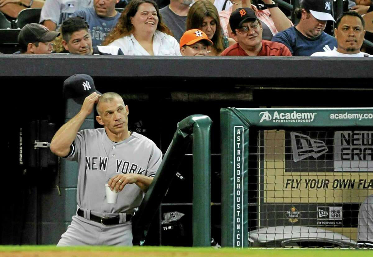 Yankees manager Joe Girardi scratches his head as he stands in the dugout in the 13th inning of a game against the Astros on Sept. 29 in Houston.