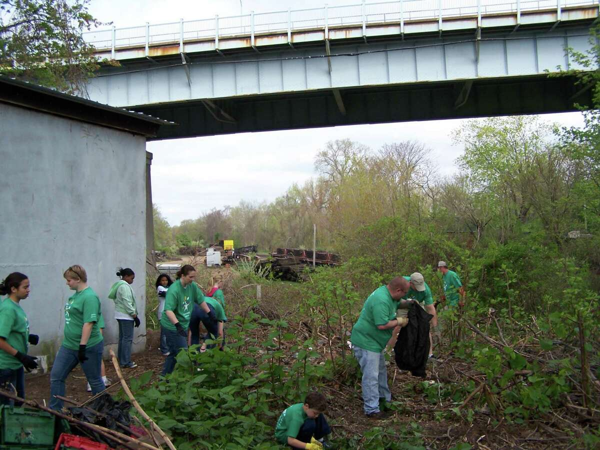 Comcast Cares volunteers clean up a back lot on Portland Street Saturday morning.