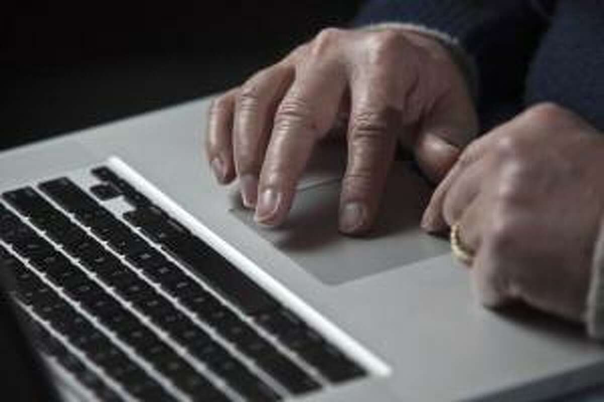 A cyber warfare expert works on his Apple laptop computer during a portrait session in Charlotte, North Carolina in this December 1, 2011 file photograph. Apple Inc was recently attacked by hackers who infected the Macintosh computers of some employees, the company said on February 19, 2013 in an unprecedented disclosure that described the widest known cyber attacks against Apple-made computers to date. REUTERS/John Adkisson/Files