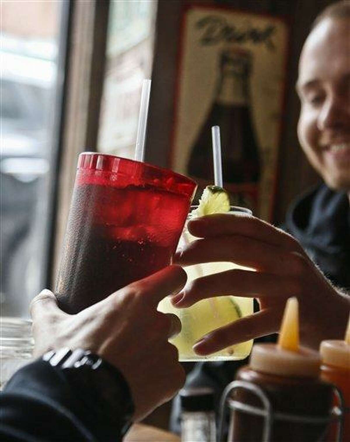 Customers at Brother Jimmy's BBQ call cheers with 24-ounce and 16-ounce beverages, March 8 in New York. Associated Press file photo