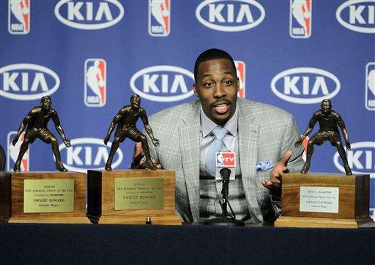 This 2011 file photo shows Orlando Magic center Dwight Howard during a news conference, with his three NBA Defensive Player of the Year awards, after he was presented with the 2010-11 award in Orlando, Fla. Howard's departure from Orlando is nearly complete. The All-Star center could be a member of the Los Angeles Lakers as soon as today, pending NBA approval of a four-team, eight-player trade also involving Denver and Philadelphia. (AP Photo/John Raoux, File)