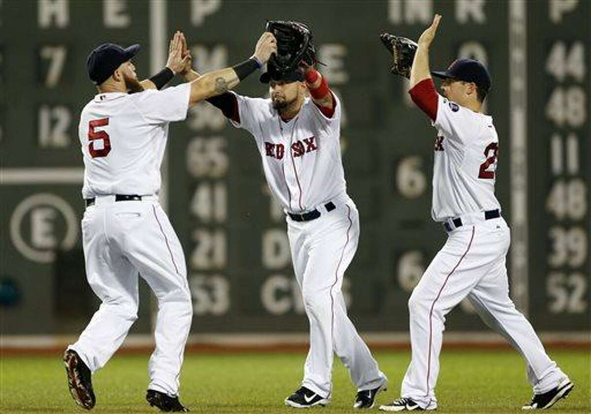 Boston Red Sox outfielders Jonny Gomes (5), Shane Victorino, middle, and Daniel Nava celebrate after the Red Sox defeated the Tampa Bay Rays 6-2 in a baseball game at Fenway Park in Boston Tuesday, July 23, 2013. (AP Photo/Elise Amendola)
