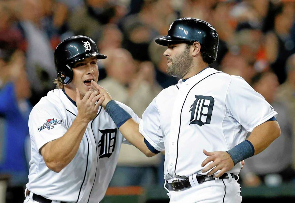 The Tigers' Andy Dirks, left, congratulates Alex Avila after they both scored on a double by Omar Infante during the eighth inning of Game 4 of the American League division series against the Oakland Athletics on Tuesday in Detroit.