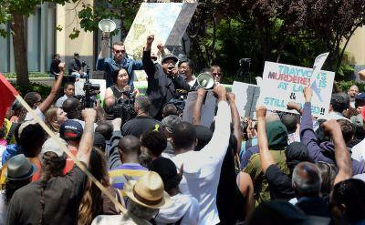 The Rev. Lennox Yearwood Jr. leads the crowd in a chant as he and Oakland Mayor Jean Quan, center left, attend a rally held at the Ronald V. Dellums Federal Building in Oakland, Calif. on Saturday, July 20, 2013.