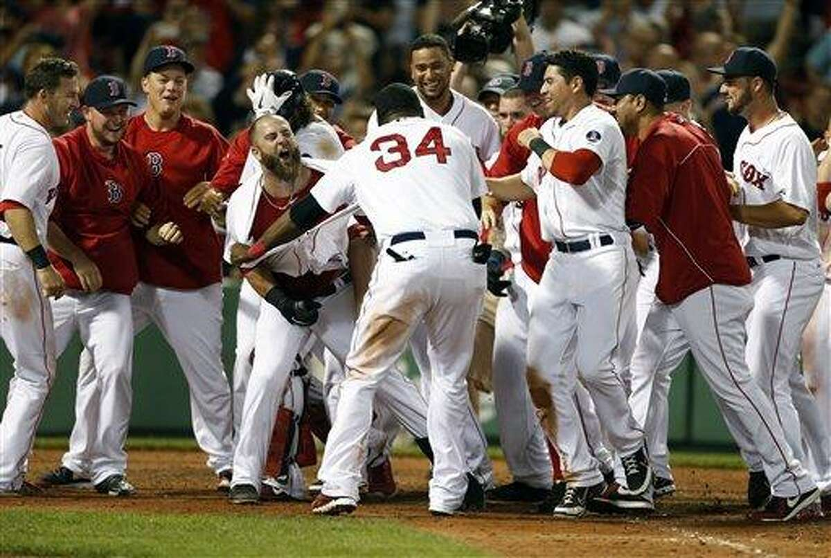 Boston Red Sox's Mike Napoli, center left, celebrates his walk-off home run in the eleventh inning of a baseball game against the New York Yankees in Boston, Monday, July 22, 2013. The Red Sox won 8-7. (AP Photo/Michael Dwyer)