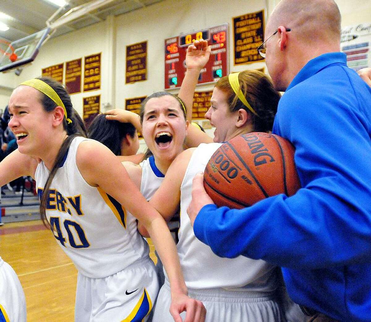 Catherine Avalone/The Middletown PressMercy Head Coach Tim Kohs rushes the court to celebrate with senior captain Maria Weselyj, center senior Liz Falcigno, at right and at left, junior Nicole Carlone following their 46-43 win over Glastonbury in the CIAC Class LL Seminfinal game at New Britain High School. Mercy will make their fourth consecutive appearance in the championship game this weekend at Mohegan Sun this weekend.