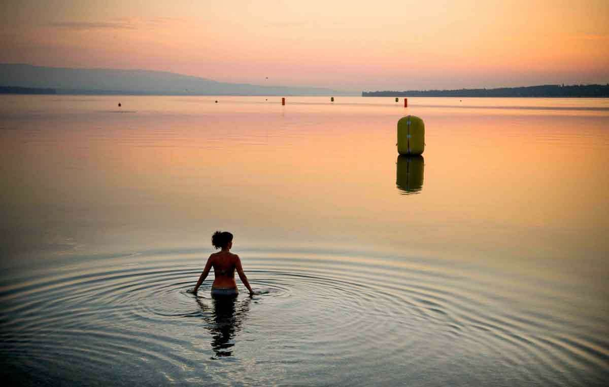 A woman takes a dip at sunrise in Lake Geneva, Geneva, Switzerland, Sunday, July 21, 2013. Temperatures are predicted to soar in Switzerland over the weekend to 34 degrees Celsius (93,2 Fahrenheit). (AP Photo/Anja Niedringhaus)