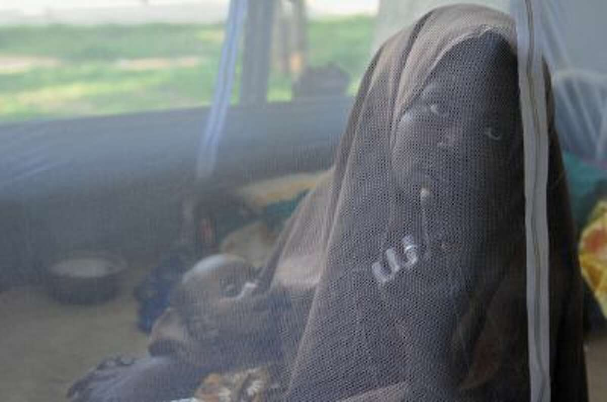Halimu Mohamed holds her 7-month-old daughter Hibo in her arms beneath a mosquito net at a hospital in Mogadishu