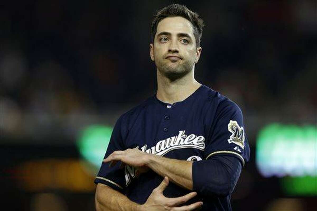 """File-This Sept. 21, 2012 file photo shows Milwaukee Brewers Ryan Braun reacting while holding his elbow after missing his swing during a baseball game against the Washington Nationals at Nationals Park, in Washington. Braun, a former National League MVP , has been suspended without pay for the rest of the season and admitted he """"made mistakes"""" in violating Major Leauge Baseball's drug policies. MLB Commissioner Bud Selig announced the penalty Monday July 22, 2013, and released a statement by the Milwaukee Brewers slugger, who said: """"I am not perfect. I realize now that I have made some mistakes. I am willing to accept the consequences of those actions."""" (AP Photo/Jacquelyn Martin, File)"""
