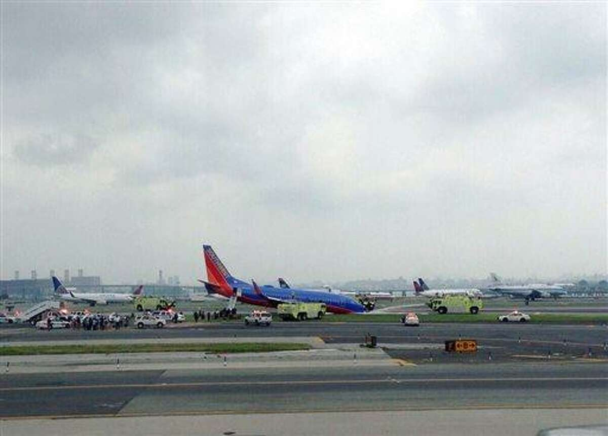 This photo provided by Bobby Abtahi, shows what officials say was a plane where the nose gear collapsed during landing at New York's LaGuardia Airport, Monday, July 22, 2013. The Federal Aviation Administration says the plane landed safely. (AP Photo/Bobby Abtahi)