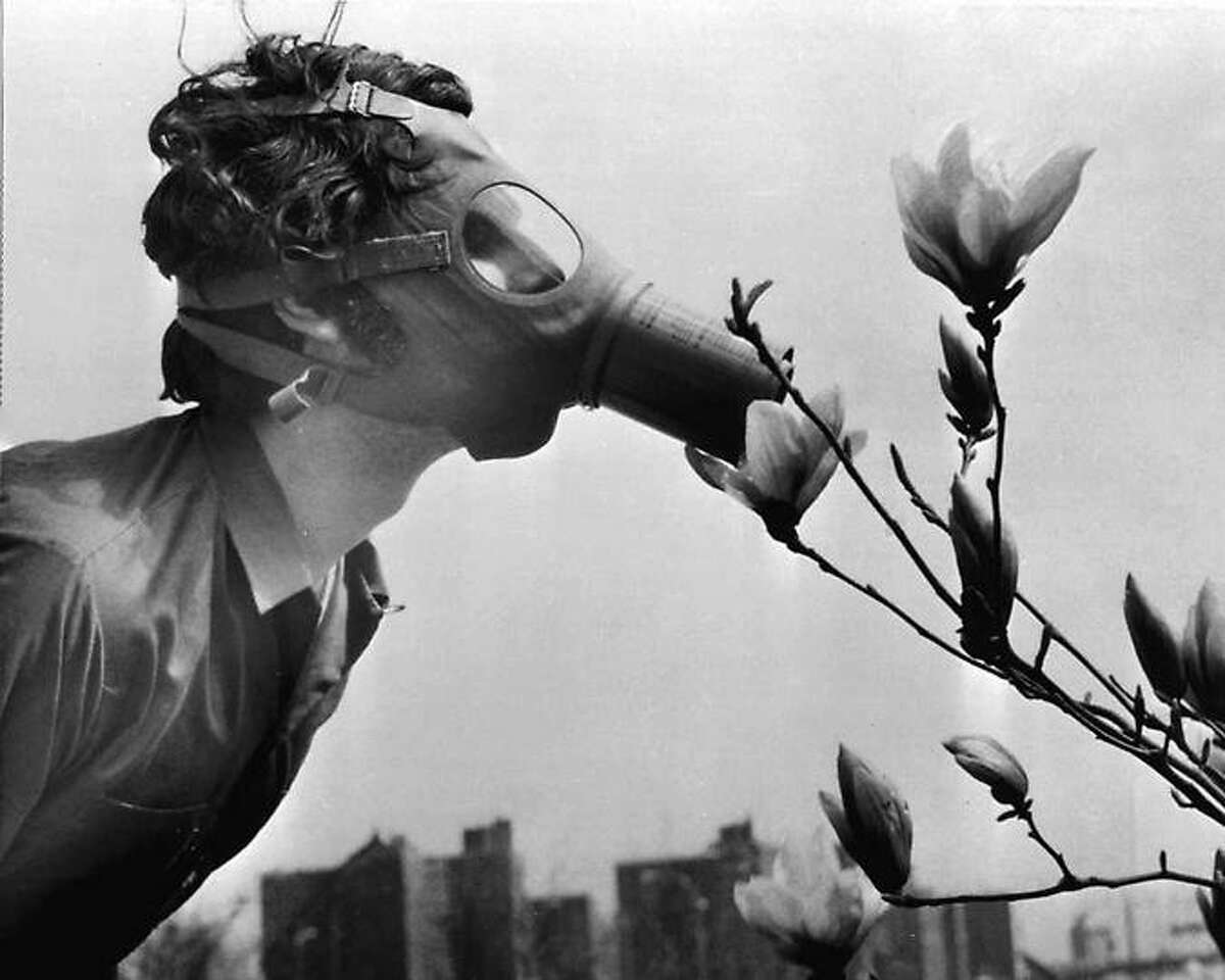 """A Pace College student in a gas mask """"smells"""" a magnolia blossom in City Hall Park on Earth Day, April 22, 1970, in New York. Associated Press"""