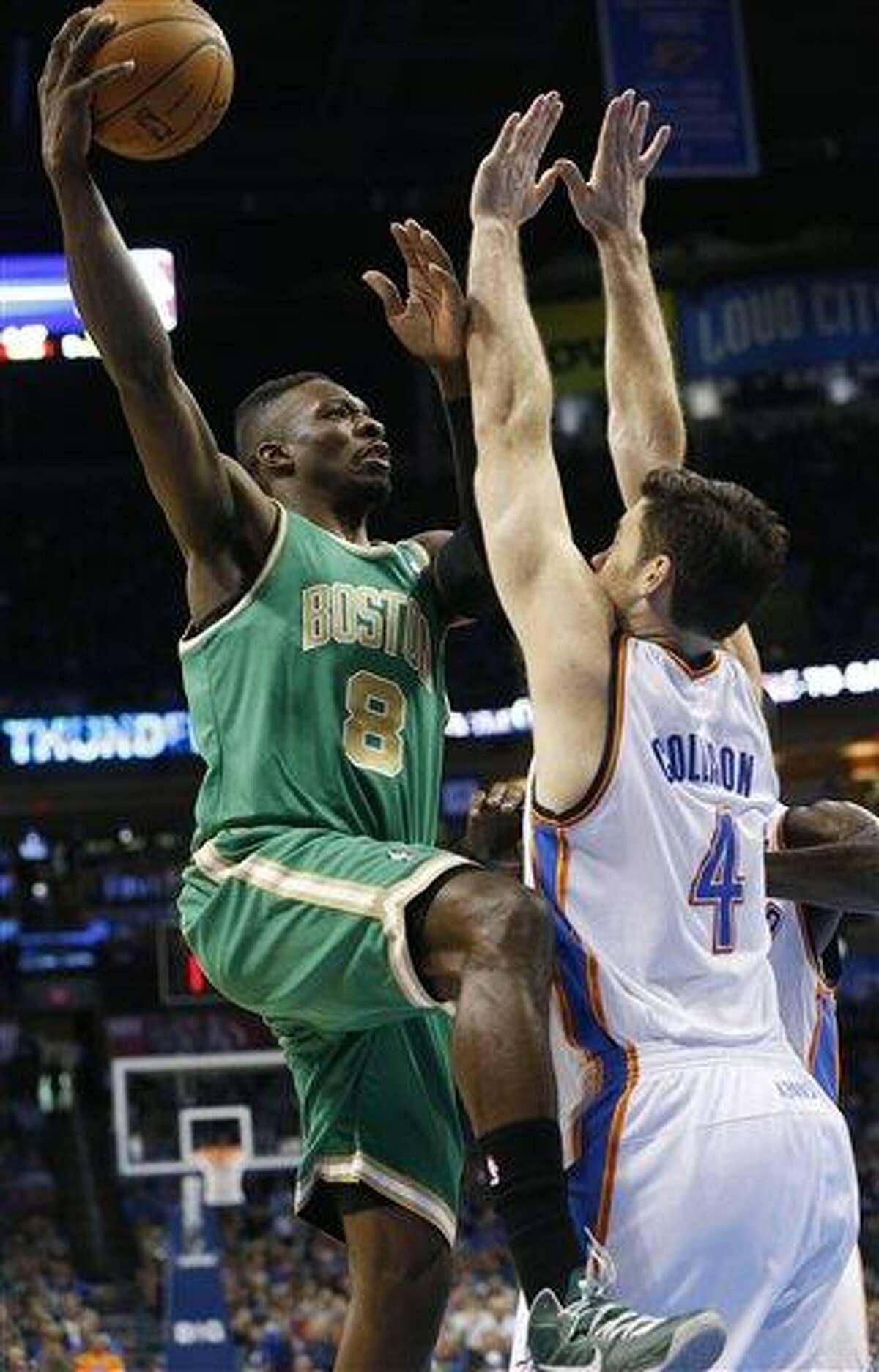 Boston Celtics forward Jeff Green (8) shoots as Oklahoma City Thunder forward Nick Collison (4) defends in the first quarter of an NBA basketball game in Oklahoma City, Sunday, March 10, 2013. Oklahoma City won 91-79 (AP Photo/Sue Ogrocki)