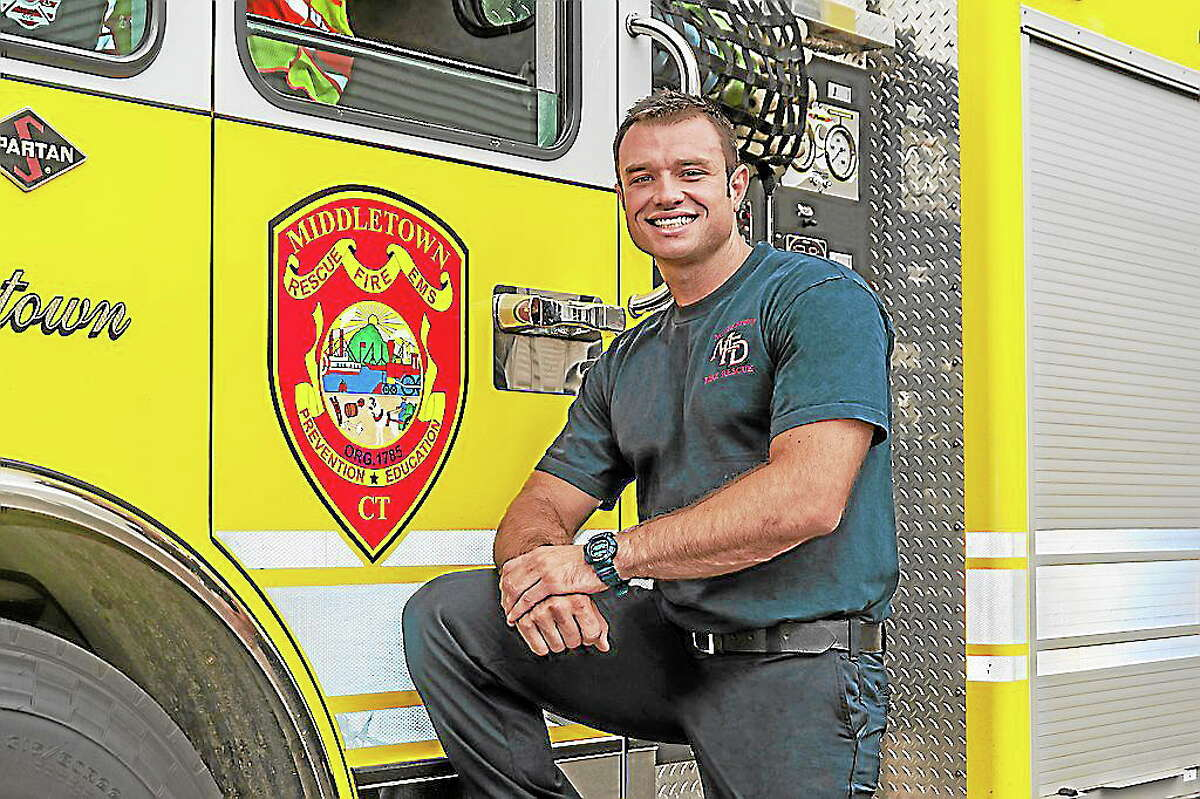 Firefighter Nick Mayo poses for his calendar shot for the annual product sold to benefit MARC.