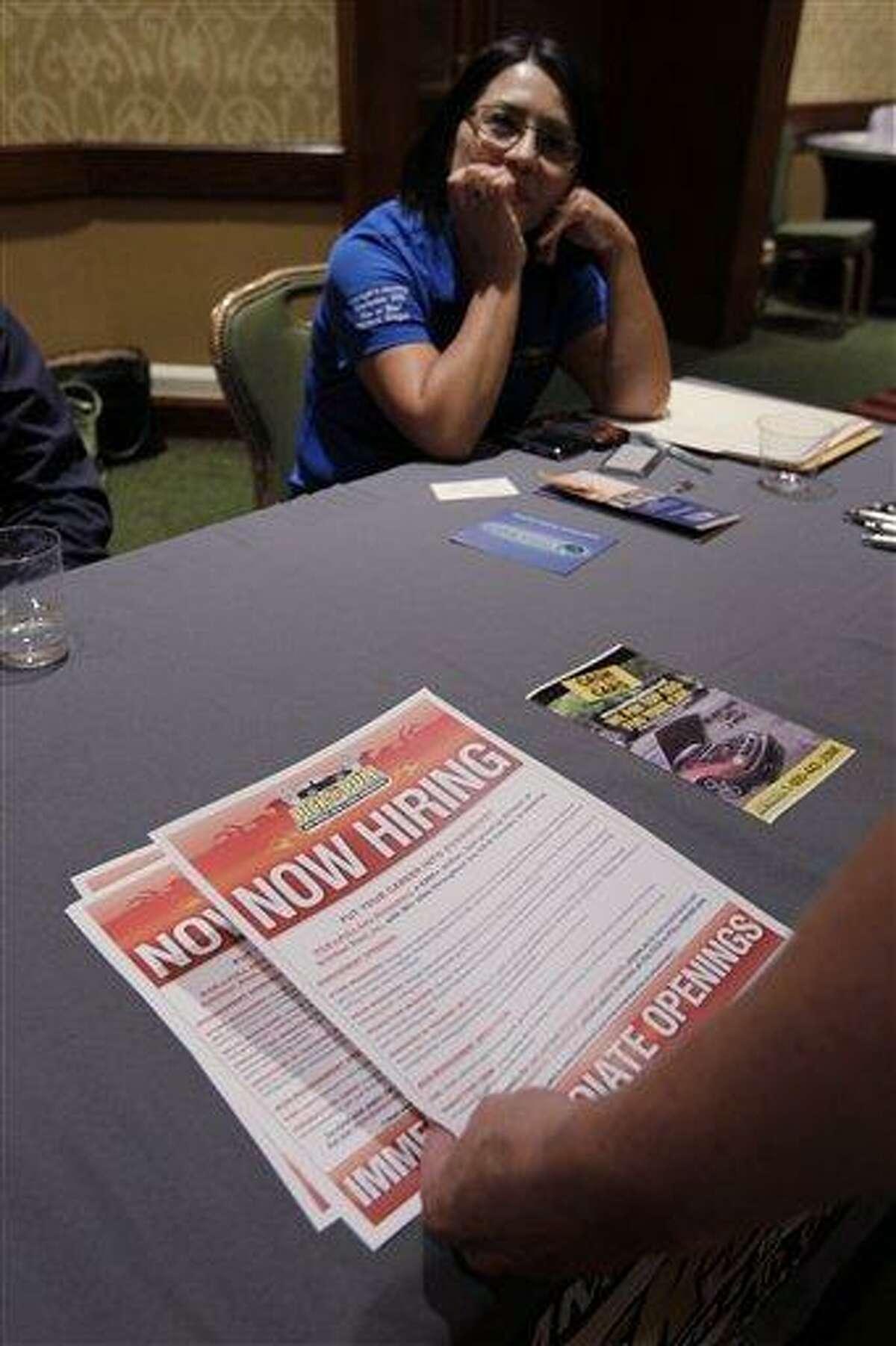 A job applicant picks up a brochure at a job fair July 25 in San Jose, Calif. Associated Press
