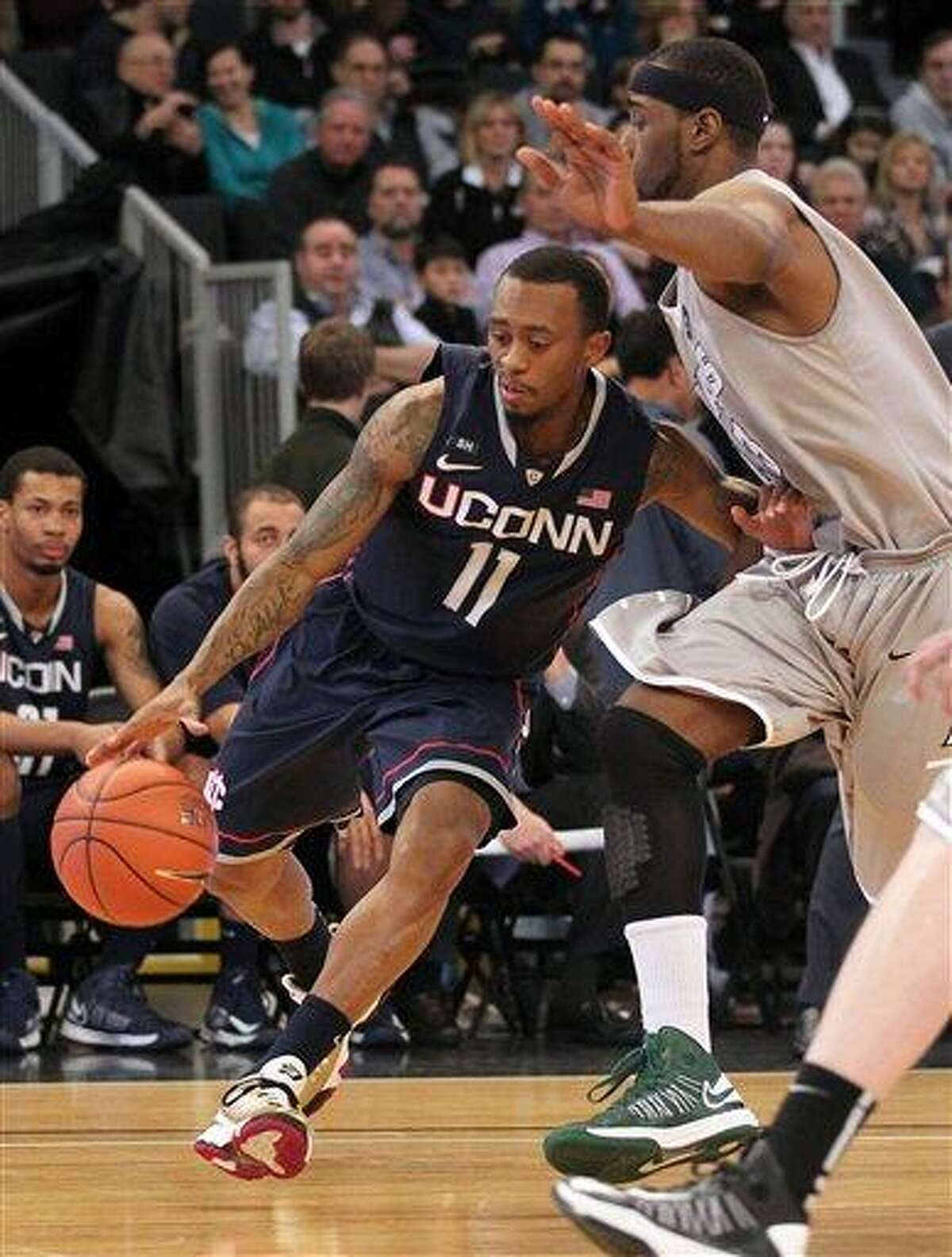 Connecticut guard Ryan Boatright (11) drives to the basket against the defense of Providence forward LaDontae Henton, right, during the second half of an NCAA college basketball game, Thursday, Jan. 31, 2013, in Providence, R.I. (AP Photo/Stew Milne)