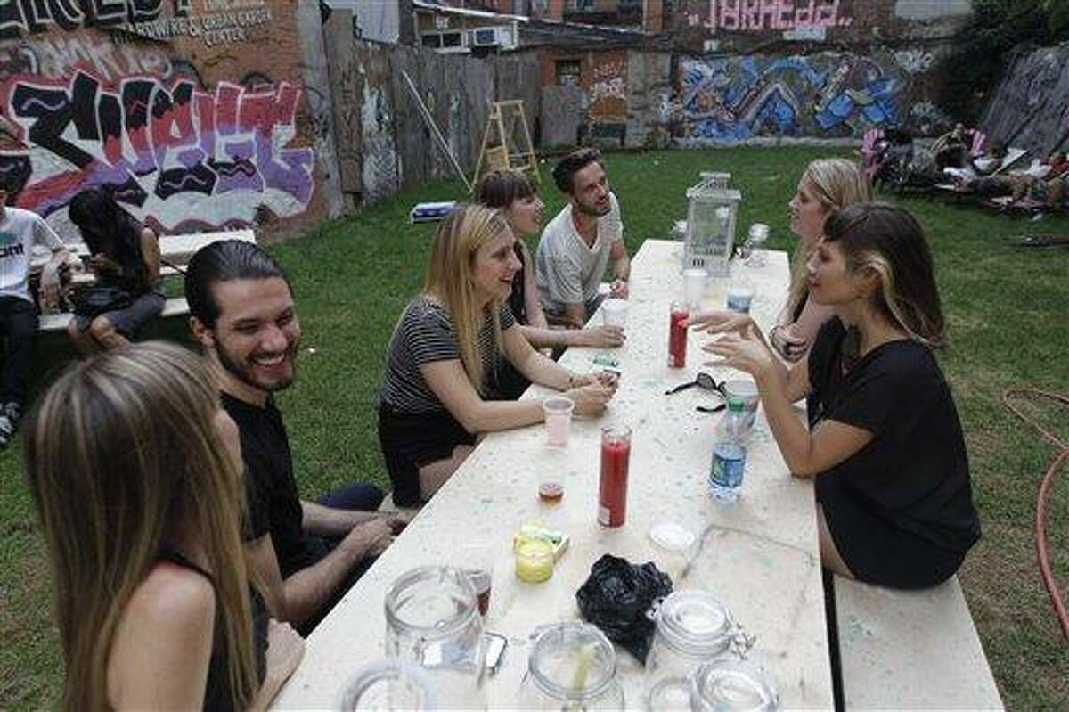 A group of people hang out at a picnic table at Timeshare Backyard July 25 on the Lower East Side of Manhattan. Associated Press