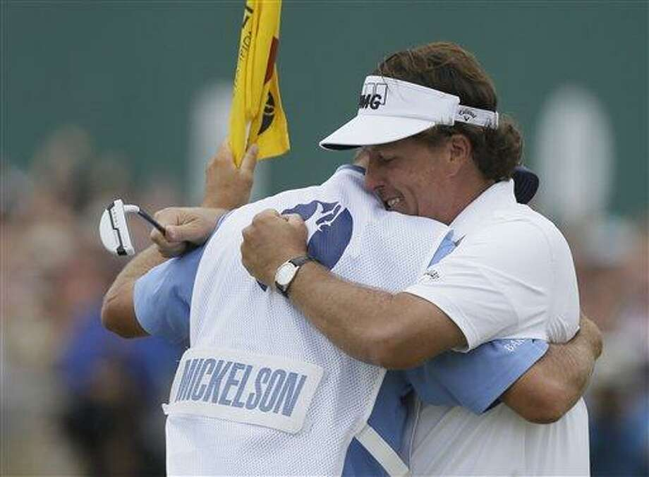 Phil Mickelson of the United States celebrates after his final putt on the 18th green with his caddie Jim Mackay during the final round of the British Open Golf Championship at Muirfield, Scotland, Sunday July 21, 2013. (AP Photo/Jon Super) Photo: AP / AP