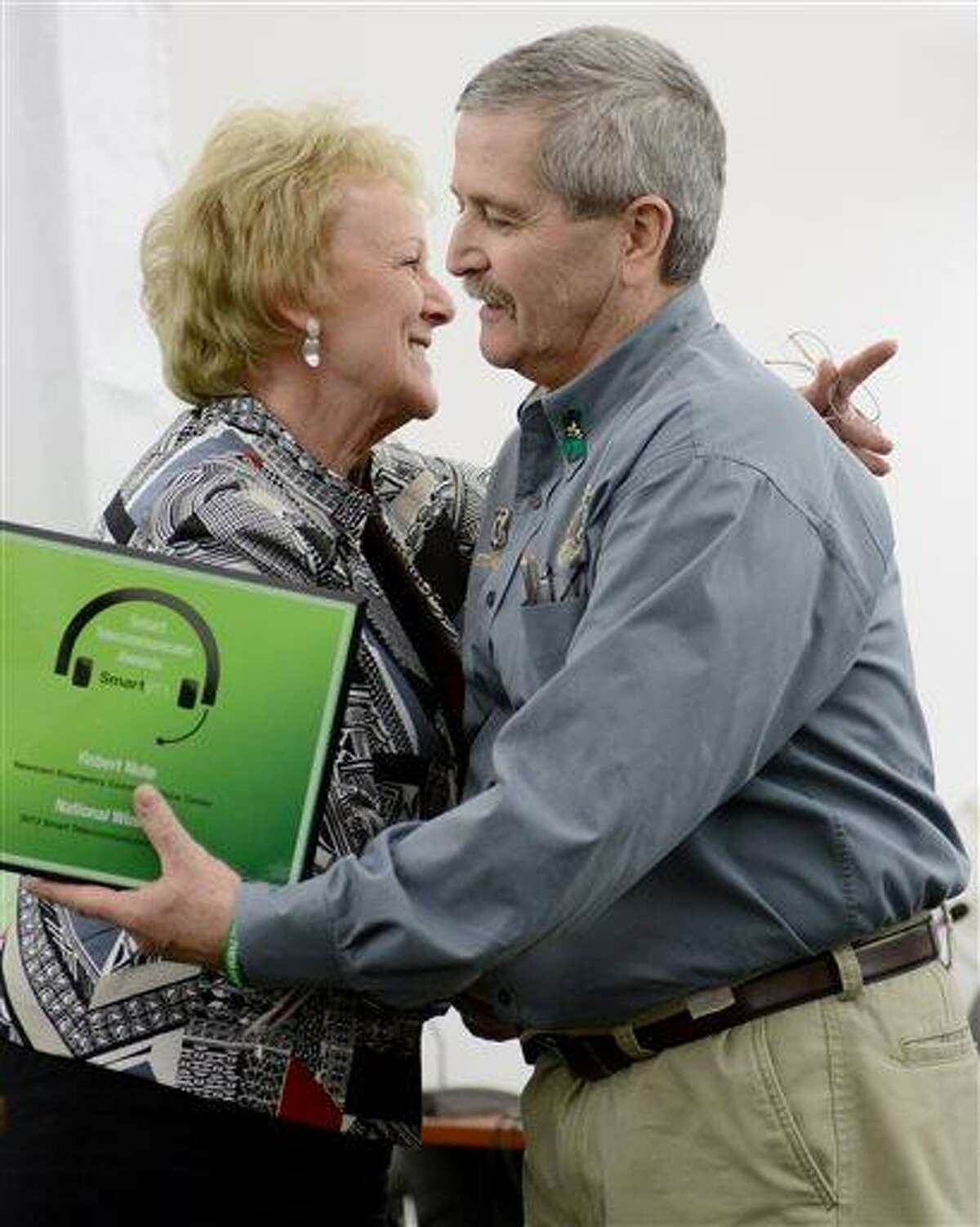 In this April 17, 2013 photo, Robert Nute, right, is congratulated by Newtown First Selectman Pat Llodra after winning an emergency telecommunications award, at the Newtown Municipal Center in Newtown, Conn. Nute, of the Newtown Emergency Communications Center, handled dispatch calls during the Sandy Hook Elementary School shooting on Dec. 14, 2012. The dispatchers at the Newtown center have won praise from officials and colleagues around the country for their role in the response to the shooting. The call center director said the staff has been lifted by the outpouring of support as the dispatchers recover emotionally, along with the community that still peppers them with calls over anything out of the ordinary. (AP Photo/The News-Times, Tyler Sizemore) MANDATORY CREDIT