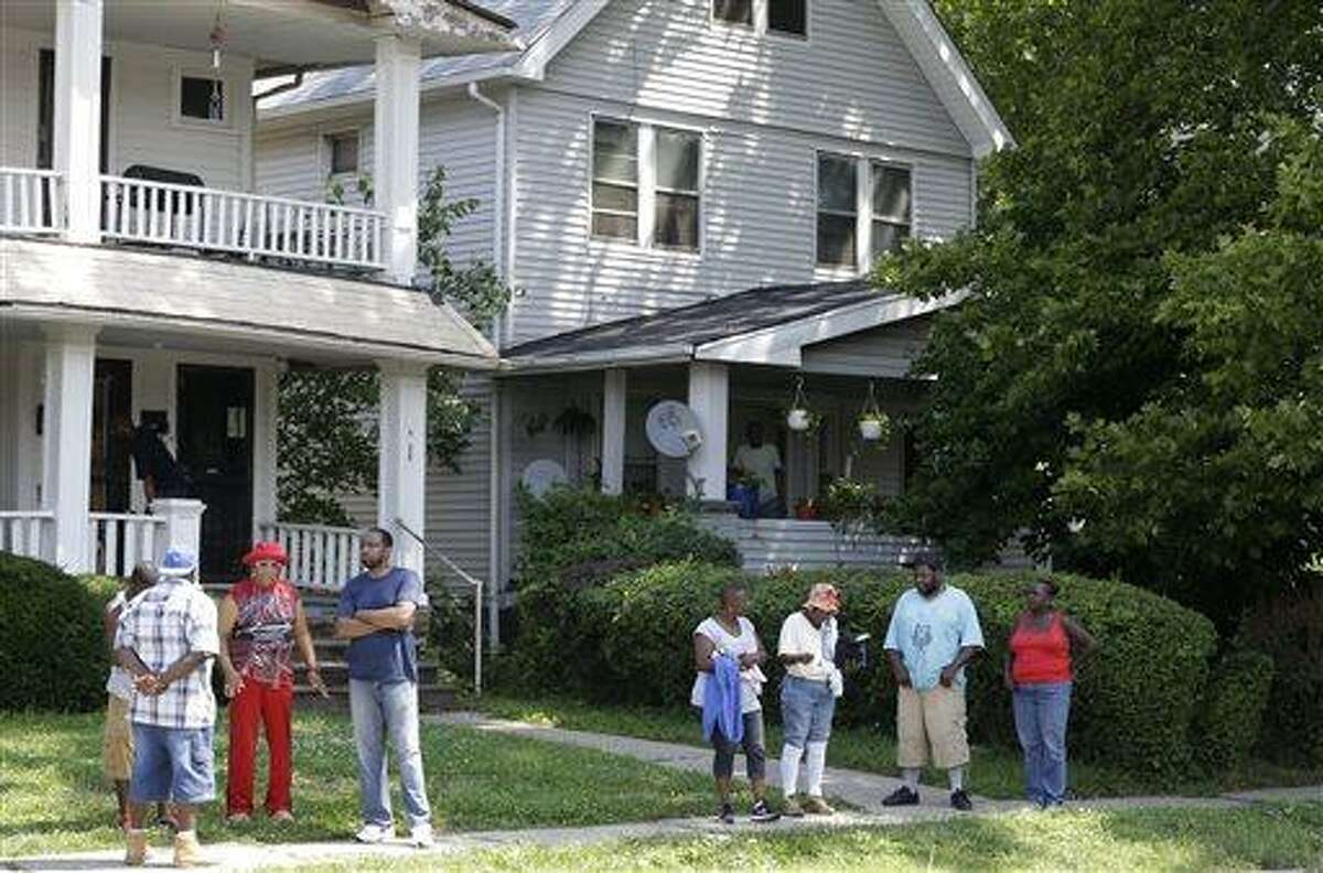 East Cleveland residents watch the scene Sunday, July 21, 2013, close to where three bodies were recently found in East Cleveland, Ohio. The bodies, believed to be female, were found about 100 to 200 yards (90 to 180 meters) apart, and a 35-year-old man was arrested and is a suspect in all three deaths, though he has not yet been charged, East Cleveland Mayor Gary Norton said Saturday.(AP Photo/Tony Dejak)