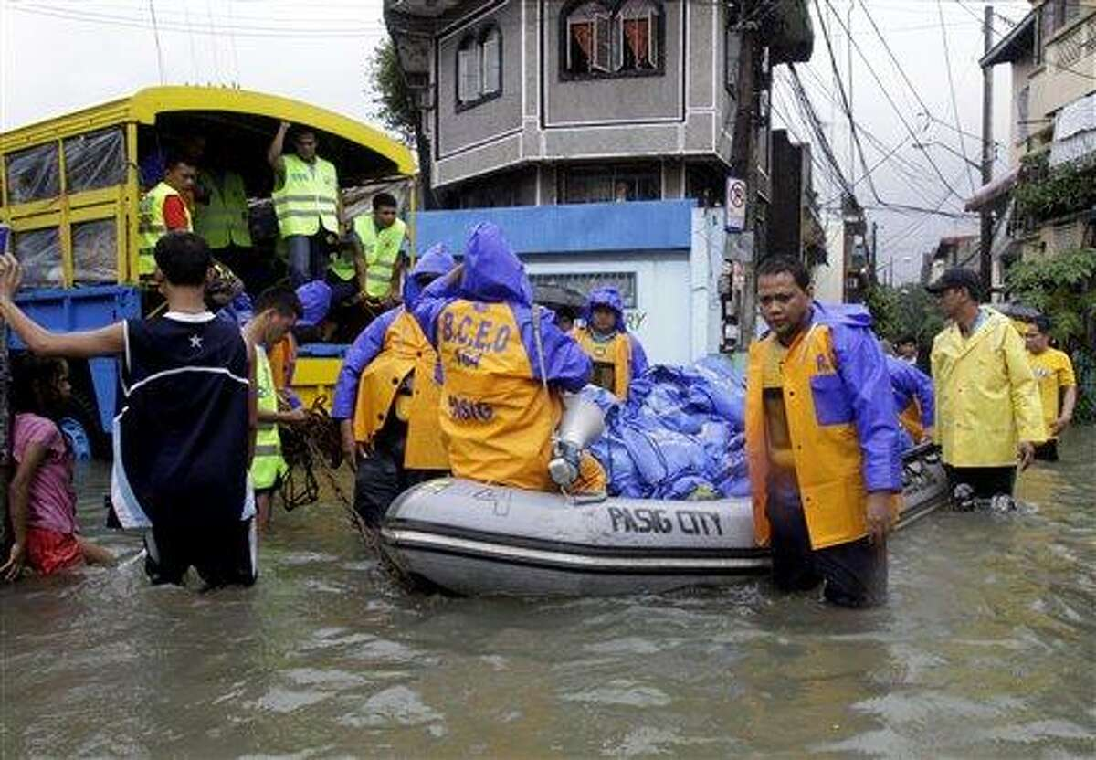 Local government employees push a rubber boat loaded with relief goods Thursday in suburban Pasig City, east of Manila, Philippines. A fresh deluge forced more evacuations along fast-rising rivers in the Philippine capital Thursday, as the city and surrounding areas struggled to deal with widespread flooding triggered by nearly two weeks of relentless rains. Associated Press