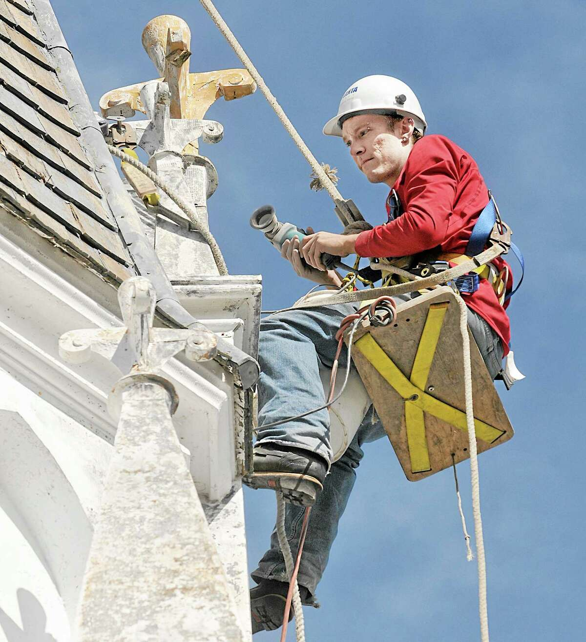 Burlington resident Mark Savsanavitch sands the steeple at St. Patrick Church on West High Street in East Hampton Tuesday afternoon. Savsanavitch, an apprentice steeple jack employed by James Pedrolini of All State Waterproofing, is contracted by Baker Liturgical Art to renovate the 80-foot high metal steeple and cedar shake roof. Catherine Avalone — The Middletown Press
