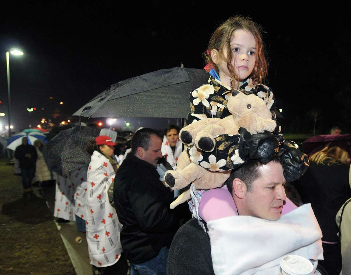Newtown--Rory Coon, 6, a first grader at Sandy Hook Elementary School, waits with her father, D'Arcy, to get into Newtown High School for a vigil with President Obama. The Red Cross provided blankets and teddy bears for those waiting to get into the vigil. Photo-Peter Casolino 12/16/12,