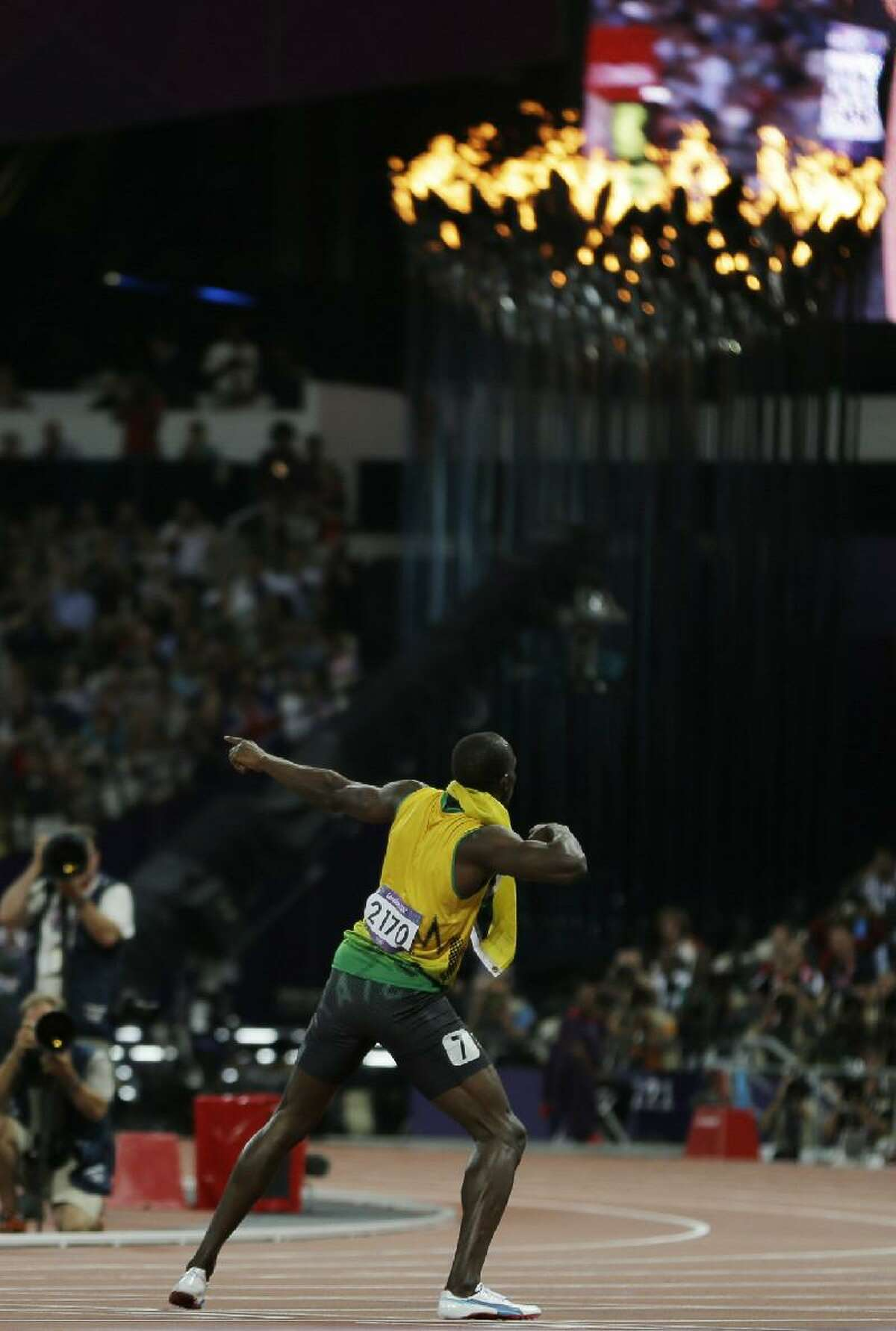 ASSOCIATED PRESS Jamaica's Usain Bolt celebrates winning the gold medal in front of the Olympic flame after the men's 200-meter final during the athletics in the Olympic Stadium at the 2012 Summer Olympics Thursday in London.