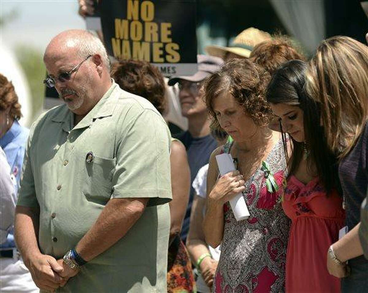 From left, Tom Sullivan, father of Aurora shooting victim Alex; Jane Dougherty, sister of Sandy Hook elementary school shooting victim Mary Sherlach; Carlee Soto, sister of Sandy Hook elementary school shooting victim Victoria; and Coni Sanders, daughter of Columbine High School shooting victim Dave Sanders, stand together during an event to honor those killed in the massacre at an Aurora, Colo. movie theater a year after the attack on Friday, July 19, 2013, in Arapahoe County, Colo. The vigil participants read a list of names of those killed in gun violence across the nation since the elementary school shooting rampage in Newtown, Conn., in December. (AP Photo/The Denver Post, Hyoung Chang)